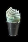 Geld in een emmer op zwarte achtergrond wordt geïsoleerd die Stock Afbeelding