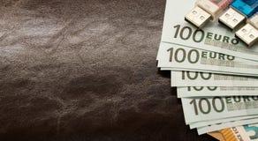 Geld in een envelop op een bruine leerblocnote stock foto