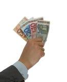 Geld in een hand die op een wit wordt geïsoleerdo Stock Foto's