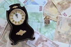 Geld, eine Uhr und ein Haus Stockfotografie