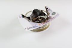 Geld in einem Aschenbecher brennt Stockfotos