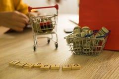 Geld in einem Korb und Münze in einer Laufkatze auf Tabelle On-line--shoppi stockbilder