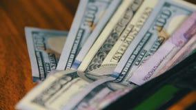 Geld in einer Geldbörse, die auf einen Holztisch sich dreht stock video