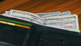 Geld in einer Geldbörse, die auf einen Holztisch sich dreht stock video footage