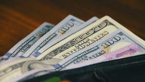 Geld in einer Geldbörse, die auf einen Holztisch sich dreht stock footage
