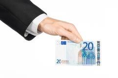 Geld en bedrijfsonderwerp: dien een zwart kostuum in houdend een bankbiljet 20 die euro op een witte achtergrond in studio wordt  Stock Foto