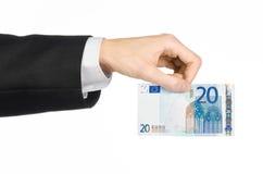 Geld en bedrijfsonderwerp: dien een zwart kostuum in houdend een bankbiljet 20 die euro op een witte achtergrond in studio wordt  Stock Afbeeldingen
