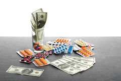 Geld en drugs op een witte achtergrond wordt geïsoleerd die Een close-up van een hoop van kleurrijke tabletten, capsules, pillen  Royalty-vrije Stock Foto