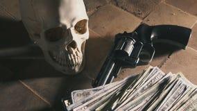 Geld en een revolver dichtbij de schedel Misdadig concept stock videobeelden