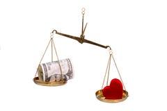 Geld en hart op schalen. Stock Afbeeldingen