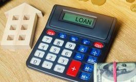 Geld en huizen op de lijst en een calculator met de woordlening Het concept het kopen van bezit in schuld Analyse van kosten en stock fotografie