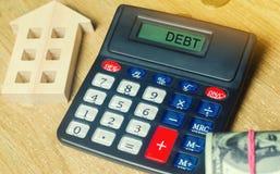Geld en huizen op de lijst en een calculator met de woordschuld Het concept het kopen van bezit in schuld Analyse van kosten en stock foto's