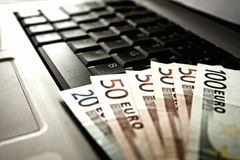Geld en laptop Stock Foto's