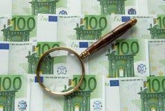 Geld en Magnifier Stock Foto
