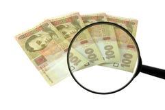Geld en meer magnifier Stock Fotografie