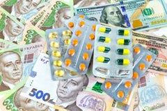 Geld en pillen: een symbool van de stijgende kost van geneesmiddelen in de wereld en in de Oekraïne royalty-vrije stock afbeeldingen