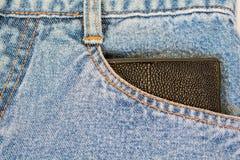 Geld en portefeuille in jeans stock fotografie