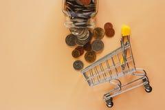 Geld en van de muntstukkenvorm glaskruik aan miniboodschappenwagentje of karretje royalty-vrije stock fotografie