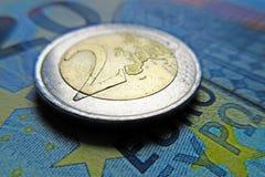 Geld- Euromünze des Euros 2 auf einer Banknote Stockfotos