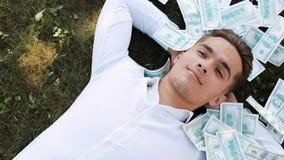 Geld fällt auf einen Lügengeschäftsmann Geldregen mit einer Reihe von hundert Dollarscheine Geschäftsart, Korruption, Gewinne stock video