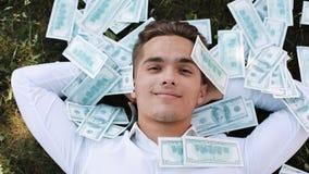 Geld fällt auf einen Lügengeschäftsmann Geldregen mit einer Reihe von hundert Dollarscheine Geschäftsart, Korruption, Gewinne stock video footage