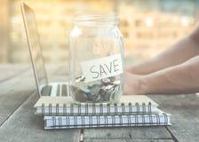 Geld für die Rettung im Glasgefäß auf Anmerkungsbuch und Laptop Stockfotografie