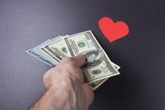 Geld für Liebe Dollar Mann ` s in Hand und im roten Herzen auf schwarzem Hintergrund Das Konzept der Prostitution Lieben für Geld Lizenzfreies Stockfoto