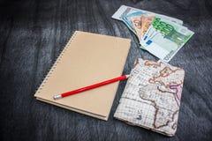 Geld-, Flugschein, Karte und Notizbuch Eurobanknotes mit Bordkarte, Karte und rotem Bleistift auf schwarzem hölzernem Hintergrund stockfoto