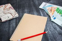 Geld-, Flugschein, Karte und Notizbuch Eurobanknotes mit Bordkarte, Karte und rotem Bleistift auf schwarzem hölzernem Hintergrund lizenzfreie stockfotos