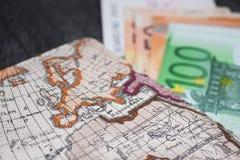 Geld-, Flugschein und Karte Eurobanknotes mit Bordkarte und Karte, auf schwarzem hölzernem Hintergrund lizenzfreie stockfotos
