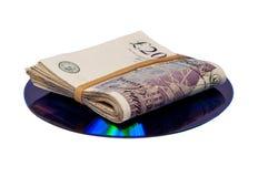 Geld gefaltet oben auf ein CD oder ein DVD stockbilder