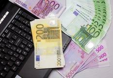 Geld gegen Laptopeuro gegen Notizbuch Stockbild
