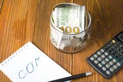 Geld in glaskruik, calculator en blocnote met woordauto bij houten achtergrond Het concept van financiën royalty-vrije stock foto