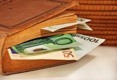 Geld in het boek Stock Afbeeldingen