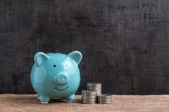 Geld of het concept van de financiënbesparing, blauw spaarvarken met stapel van c stock afbeelding