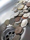 Geld hinunter den Abfluss Stockbilder
