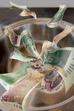 Geld hinunter den Ablaß Lizenzfreies Stockbild