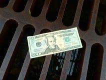 Geld hinunter den Ablaß Lizenzfreie Stockfotos