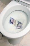 Geld hinunter die Wanne Stockbilder