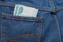Geld in Ihren Taschenjeans Stockfotos