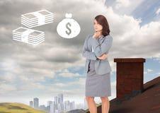 Geld-Ikonen und Geschäftsfrau, die auf Dach mit Kamin im Land mit Stadt im Abstand stehen Stockfotografie