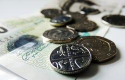Geld- Münzen und eine Banknote, mit Fokus auf den 5 Pennys prägen Lizenzfreies Stockbild