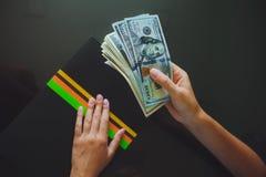 Geld in menselijke handen, vrouwen die dollars geven Stock Afbeelding
