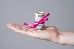 Geld mit Band in der männlichen Hand auf einem grauen Hintergrund Stockfotos