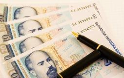 Geld mit einer Feder Lizenzfreies Stockfoto