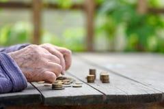 Geld, muntstukken, de grootmoeder op pensioen en het concept het leven, minimum - de gerimpelde handen van de oude vrouw raken mu stock foto's