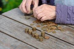 Geld, muntstukken, de grootmoeder op pensioen en het concept het leven, minimum - de gerimpelde handen van de oude vrouw raken mu stock fotografie