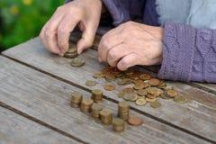 Geld, muntstukken, de grootmoeder op pensioen en het concept het leven, minimum - de gerimpelde handen van de oude vrouw raken mu royalty-vrije stock afbeelding