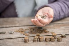 Geld, muntstukken, de grootmoeder op pensioenen en een concept een het leven minimum - in handen van de oude vrouw isn ` t genoeg royalty-vrije stock afbeelding