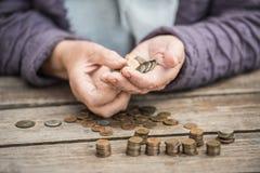 Geld, muntstukken, de grootmoeder op pensioenen en een concept een het leven minimum - in handen van de oude vrouw isn ` t genoeg stock foto